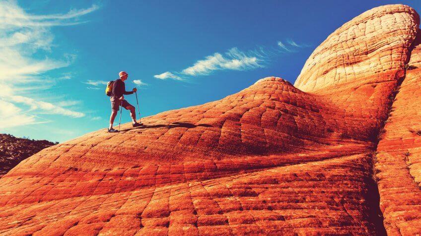 man hiking rock formation in Utah
