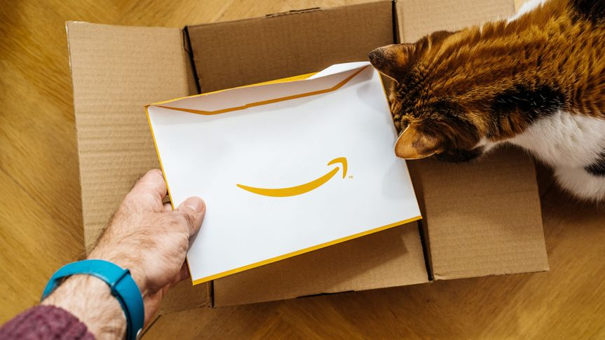 man opening up Amazon box with cat