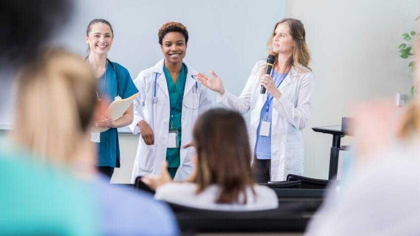 Confident diverse female healthcare professionals speak at a healthcare conference.