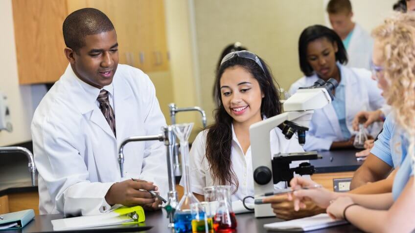 African American mid adult man is teacher in modern science lab classroomm.