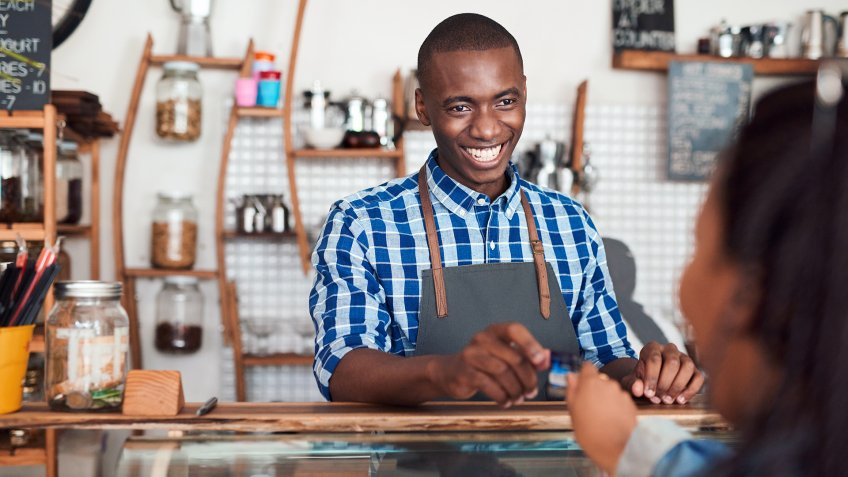 Smiling barista standing behind a counter in a cafe taking a credit card from a customer to pay for her purchase - Image.