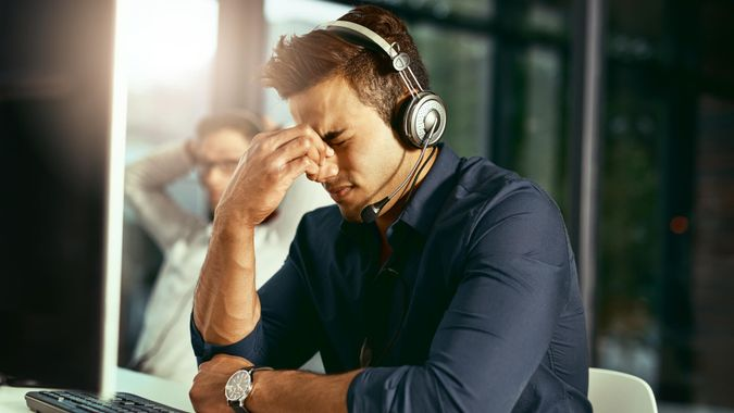 Shot of a young call centre agent looking stressed out while working in an office.