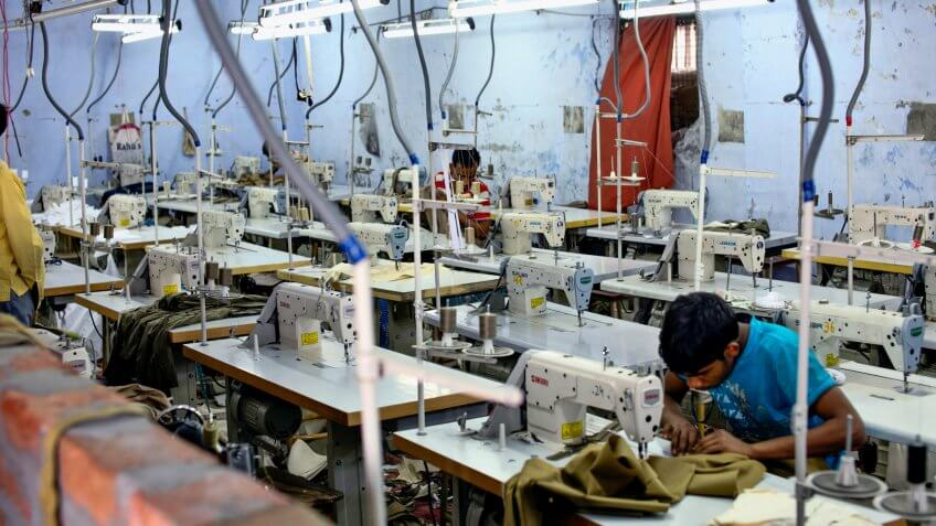 unidentified tailors sewing some clothes in a factory near ludhiana, punjab, india on 10 october 2013.