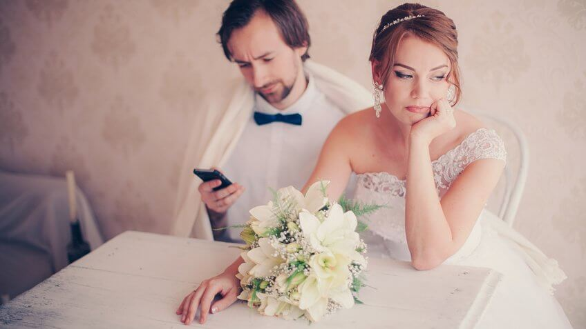 the bride upset the groom is distracted by the phone during a wedding photo session, careless couple.