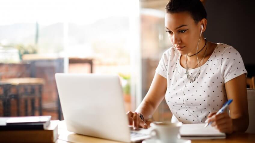 Attractive young woman working on laptop and taking notes at a cafe.