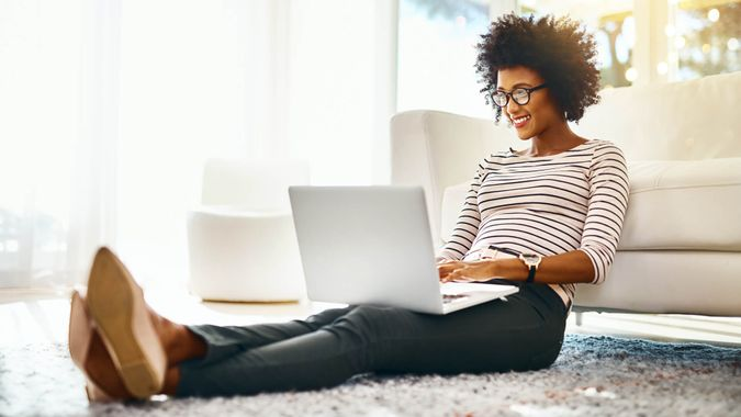 Shot of a cheerful young woman doing online shopping on her laptop while being seated on the floor at home.