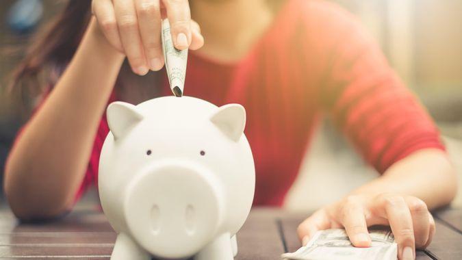 woman putting money in savings bank