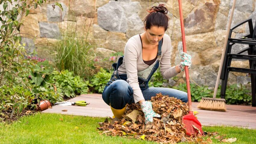 Young woman raking leaves autumn pile garden veranda housework sweeping.