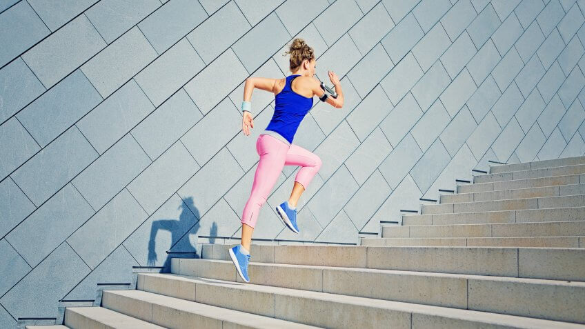 Girl is runing on the city stairs and listening the music.