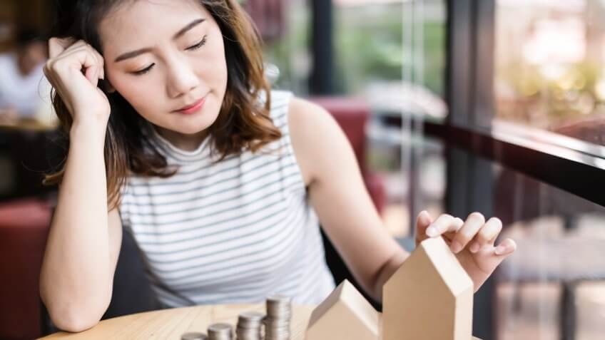 business young woman look at paper house model and coins money stack on wooden table.