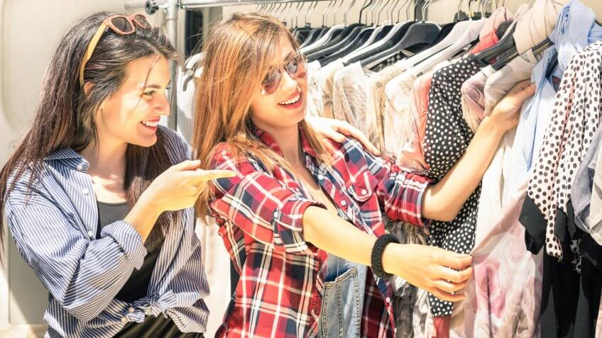 Young beautiful women at the weekly cloth market - Best friends sharing free time having fun and shopping in the old town in a sunny day.