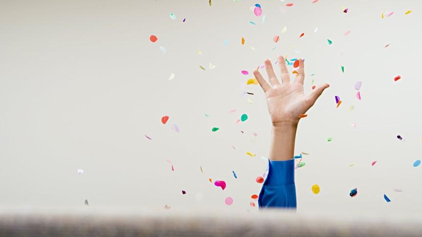 Businessman throwing confetti in the air.