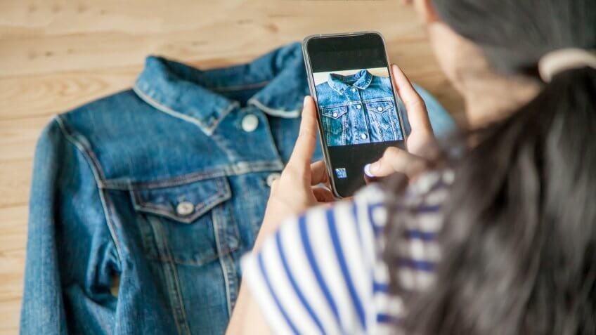 woman taking photo of denim jacket in a store