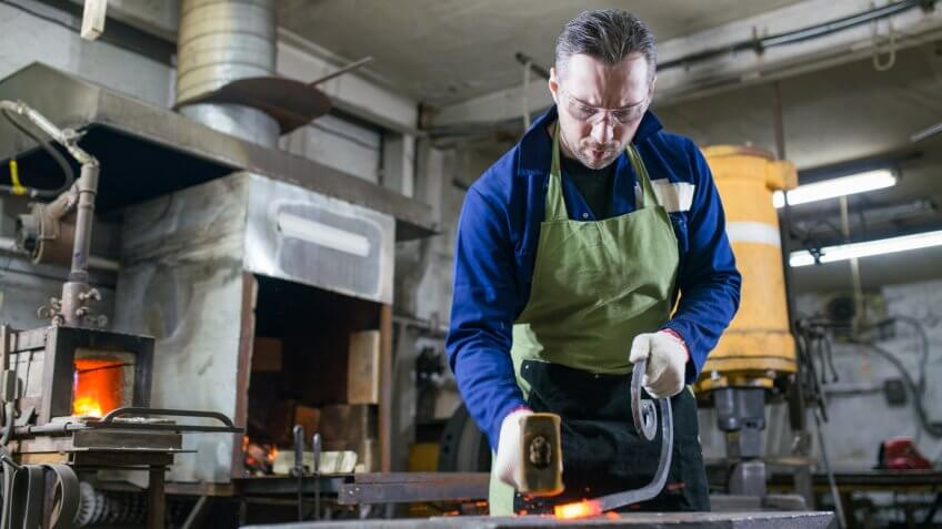 a metalsmith forges metal