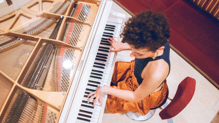 Young beautiful caucasian woman plays piano.