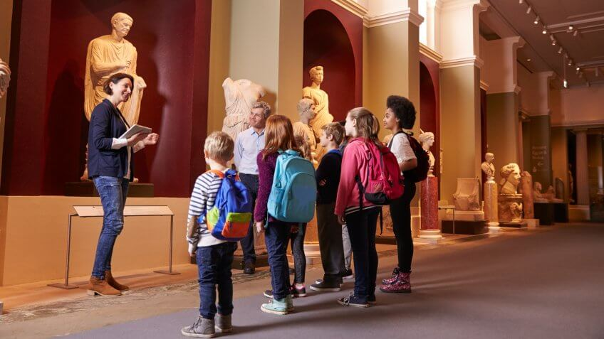 Pupils And Teacher On School Field Trip To Museum With Guide.