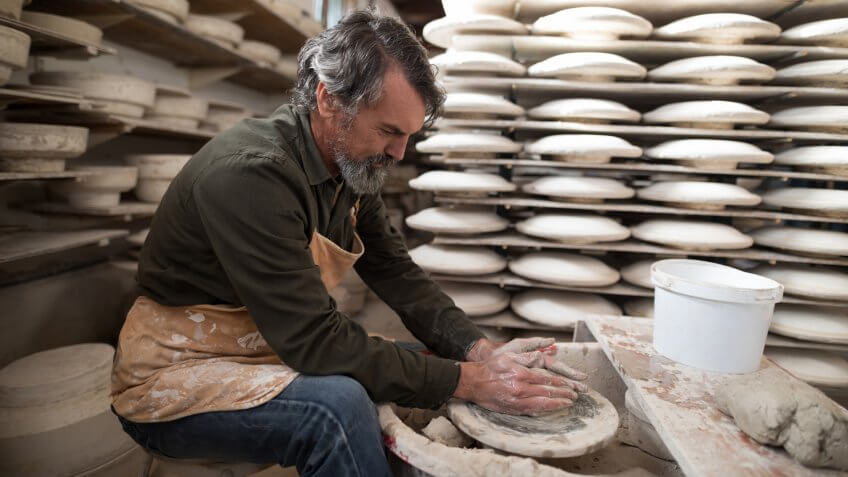 Male potter molding a clay in pottery workshop.