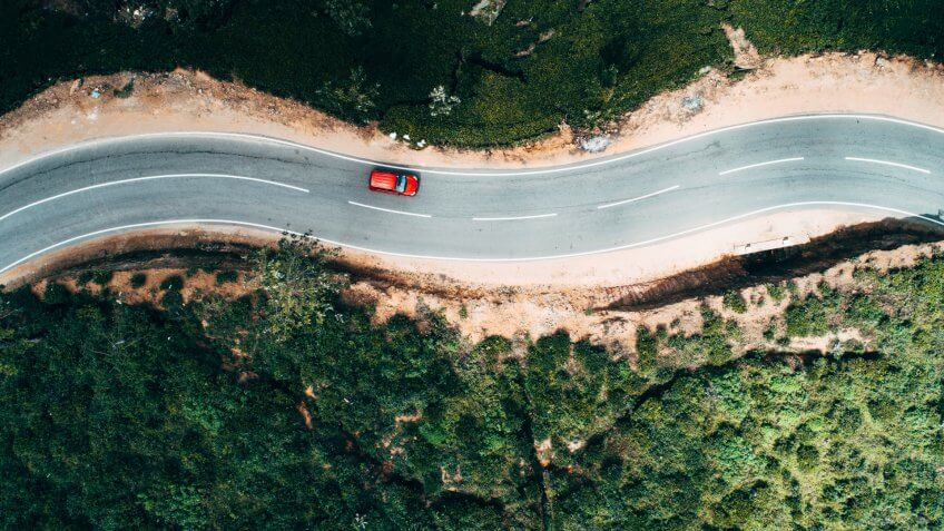 Aerial view on  red car on the road near green tea plantation in mountains in Sri Lanka.