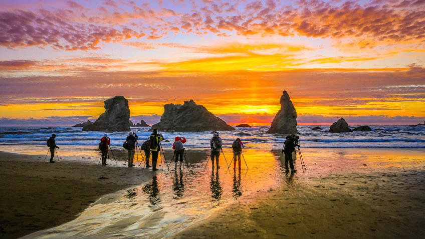 Bandon Beach-Oregon State, June 02 2017 : A group of photographers taking photos of the rock formations and sun setting on Bandon Beach, USA.