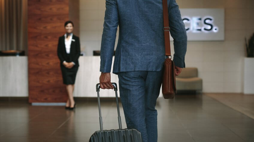 Businessman carrying suitcase while walking in hotel lobby.