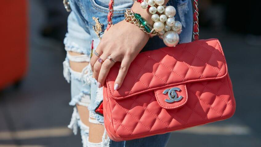 MILAN - SEPTEMBER 25: Woman with red Chanel bag and big pearls bracelet before Stella Jean fashion show, Milan Fashion Week street style on September 25, 2016 in Milan.