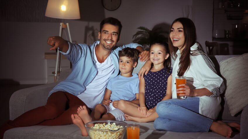 Happy family watching TV on sofa at night
