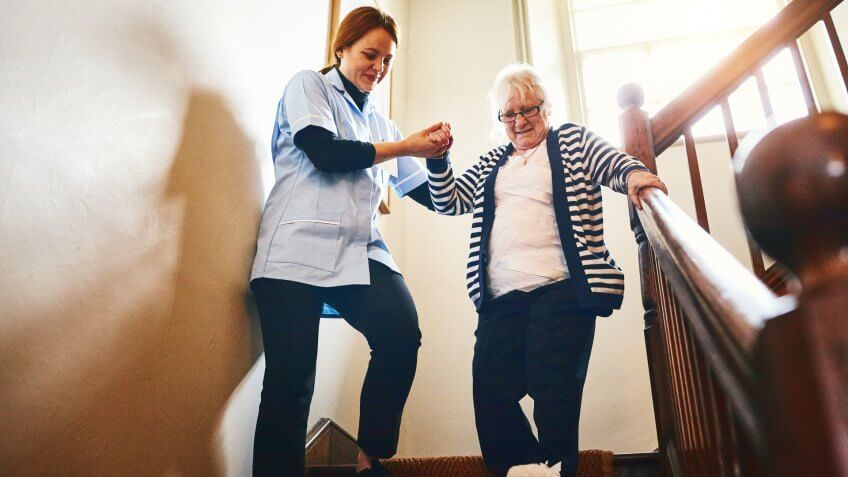 Young female caregiver helping senior woman walking down stairs at home.