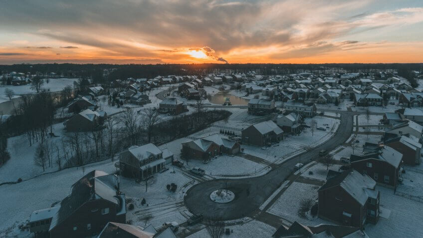 A drone shot over a neighborhood after snowfall with the sunsetting in Kentucky.