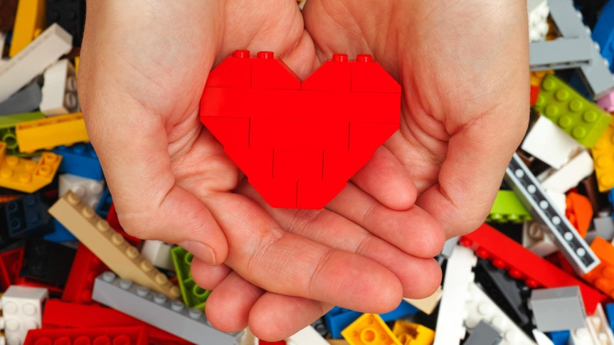 Tambov, Russian Federation - September 07, 2015: Lego red heart in woman hands with Lego blocks background.