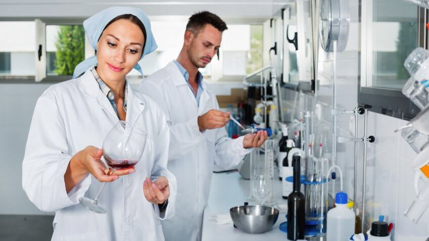 Two young efficient  researchers in white coat checking wine acidity and sugar saturation in chemical laboratory.