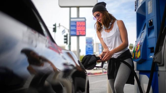 Young woman refueling car at the gas station.