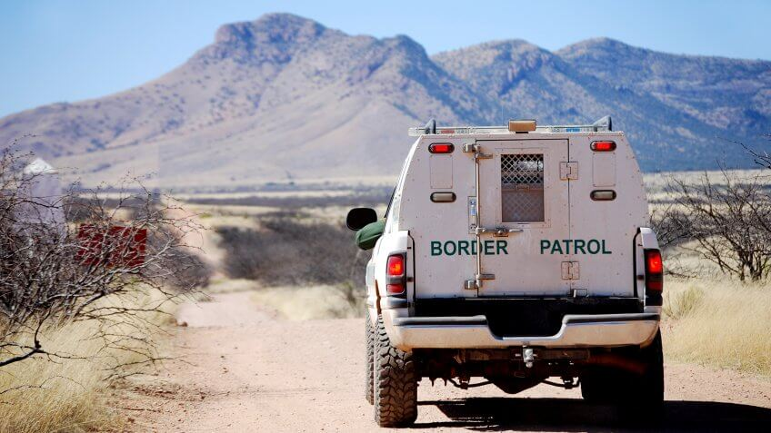 Back of a border patrol truck driving on a dirt road along the Mexican border in Arizona, with mountains in the background.