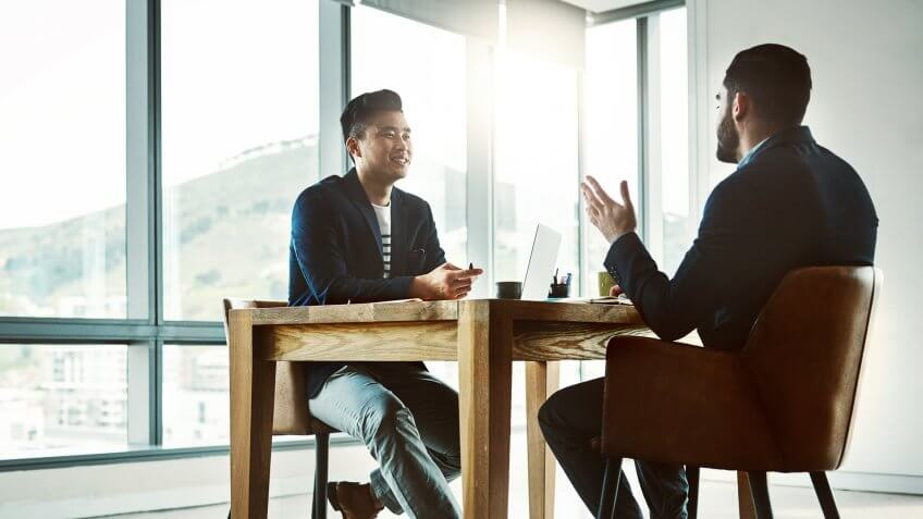 Shot of two young businessmen having a discussion at a desk in a modern office.