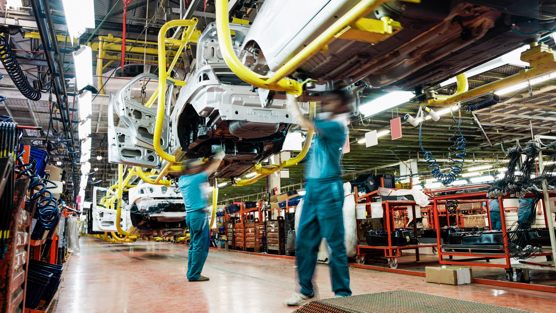 Two workers wearing green shirts and blue pants work underneath a car in an automobile factory.