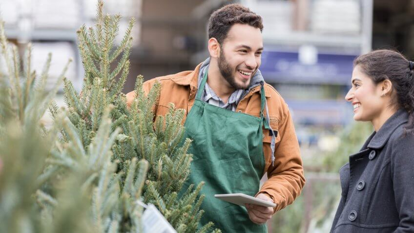Confident male Christmas tree lot owner helps a female customer pick out a Christmas tree for her home.