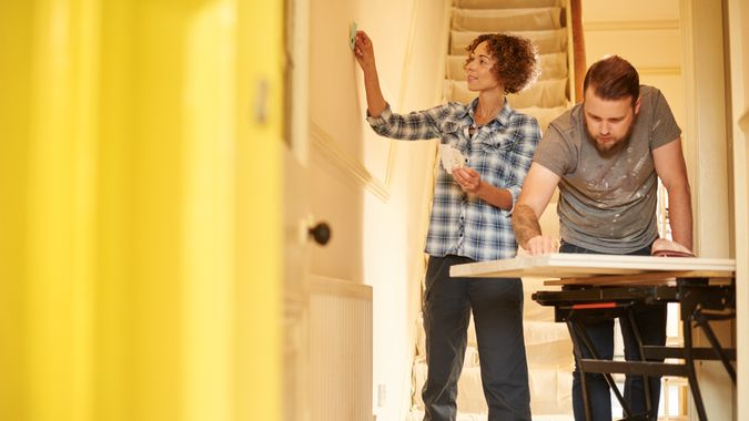 A young couple doing up their hallway in the old house they have bought .