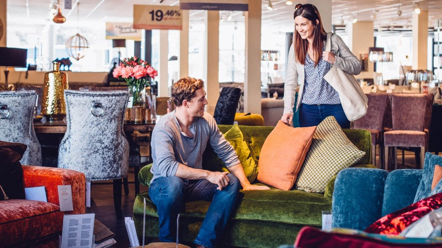 Young women out shopping with her husband in a furniture shop.