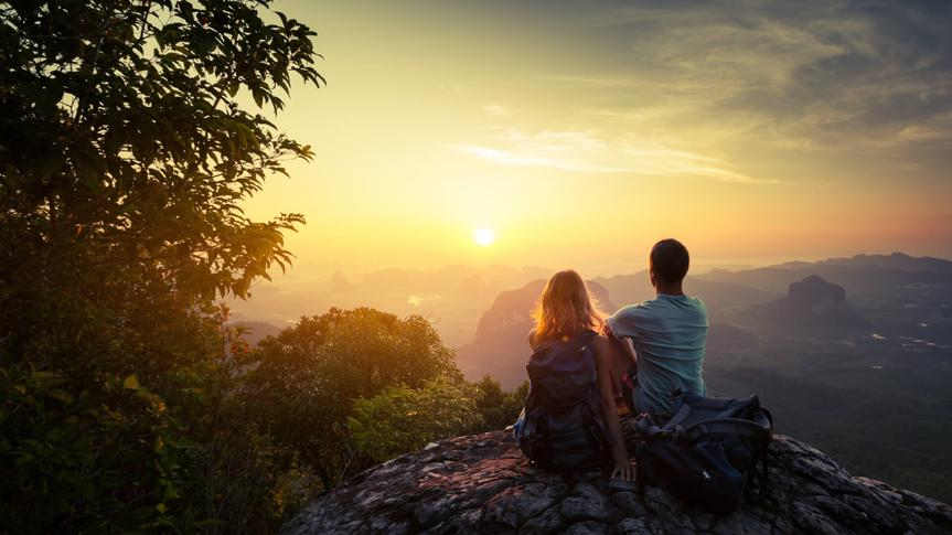 Two hikers on top of the mountain enjoying sunrise over the tropical valley.