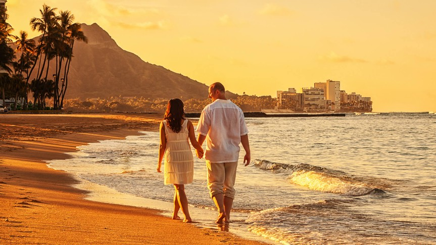 Photo of a happy young couple walking hand-in-hand on Waikiki beach at sunrise.