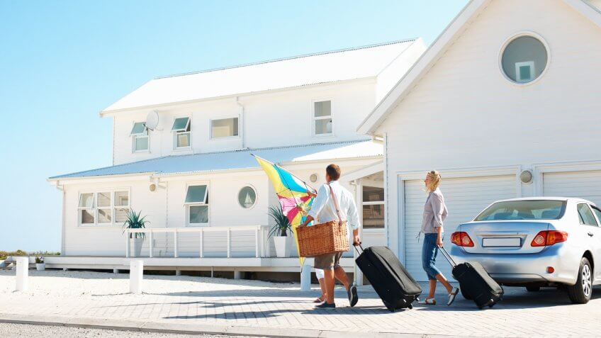 Young family arriving at their holiday beach house.