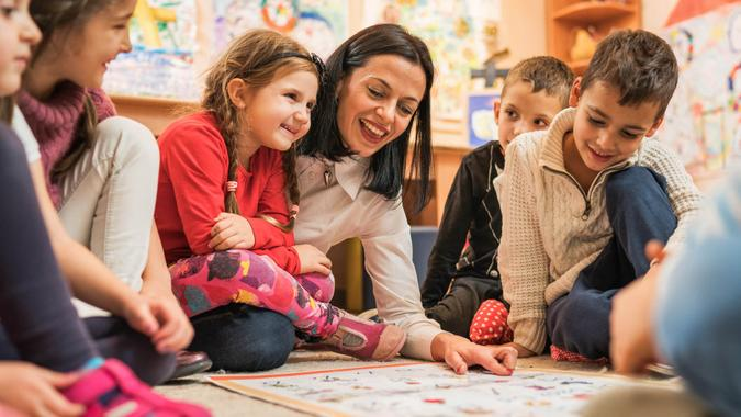 Happy female teacher teaching group of small kids in a preschool.