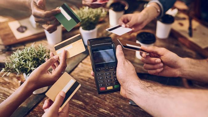 High angle shot of a group of friends offering their bank cards to pay the bill at a cafe.