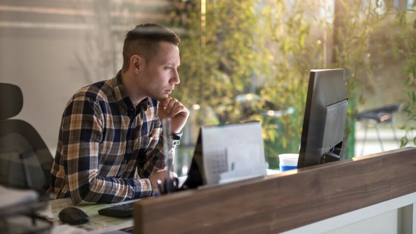 Young pensive businessman holding hand on chin and looking at desktop PC in the office.