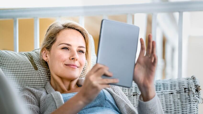 A photo of happy young woman using digital tablet on balcony.