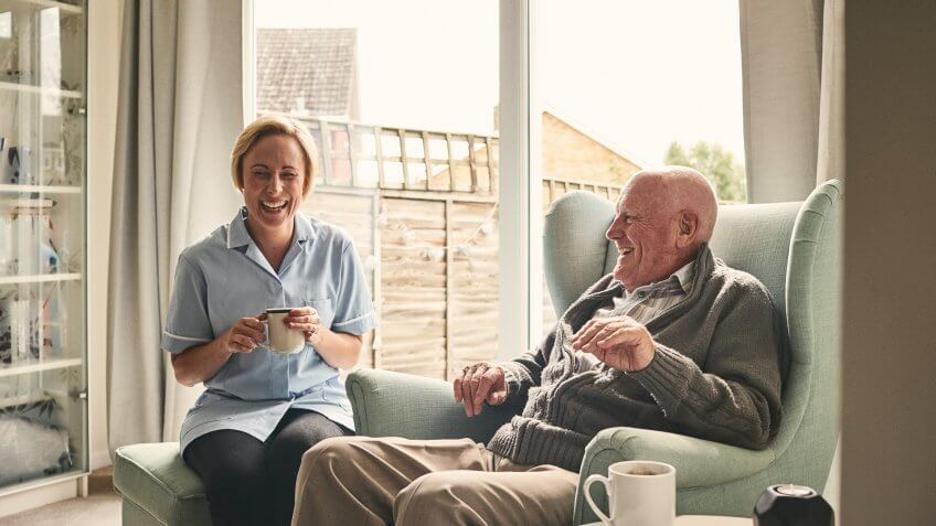 Indoor shot of smiling senior man and female carer enjoying coffee in living room.