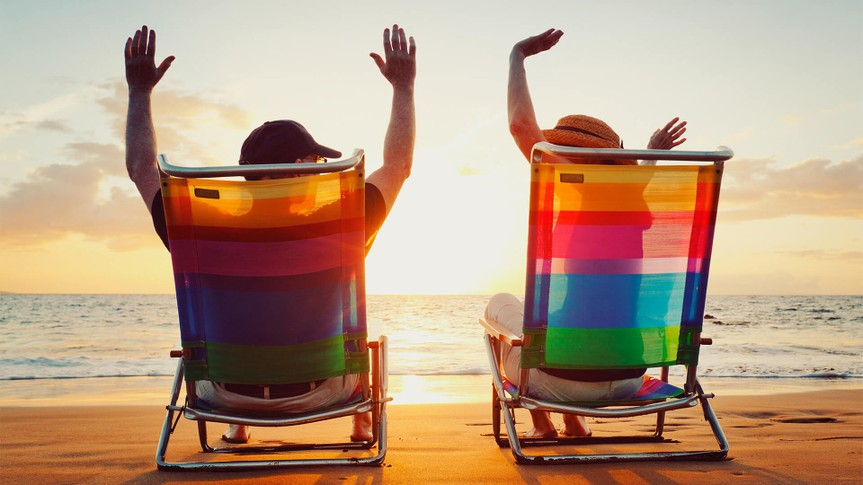 man and woman sitting on beach chairs at sunset