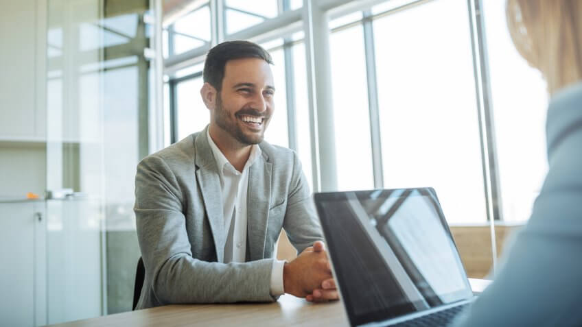 Young man smiling during a job interview.