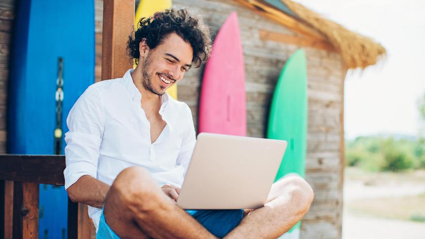 Cheerful young man using laptop with surfing boards at the background.