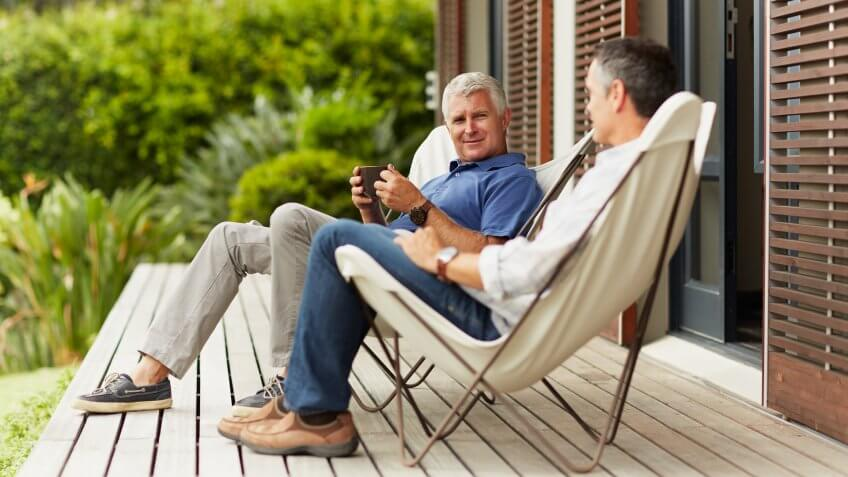 Full length of mature male friends spending leisure time at yard.