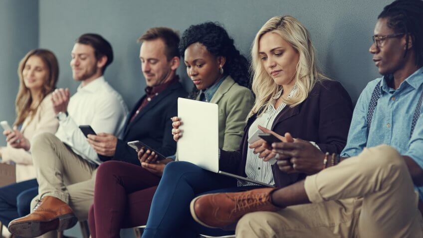 Shot of a group of businesspeople using different wireless devices while waiting in line for an interview.